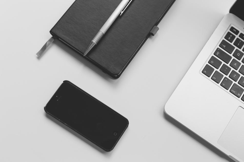 Black smartphone, black notebook, gray pen & laptop on white desk. Liam Hennessy, Digital Strategist.
